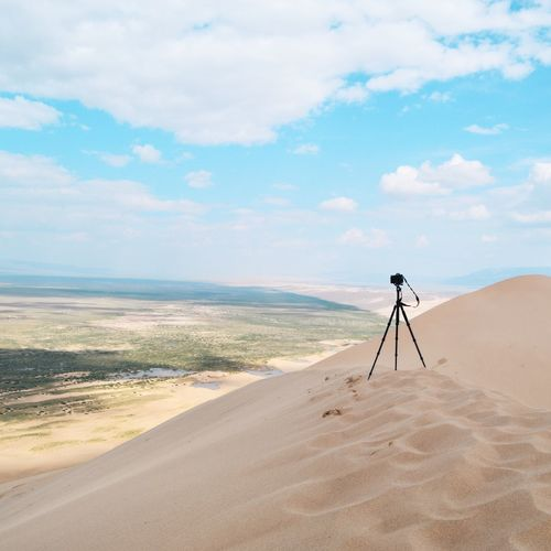 Tripod On Sand In Desert Against Cloudy Sky During Sunny Day