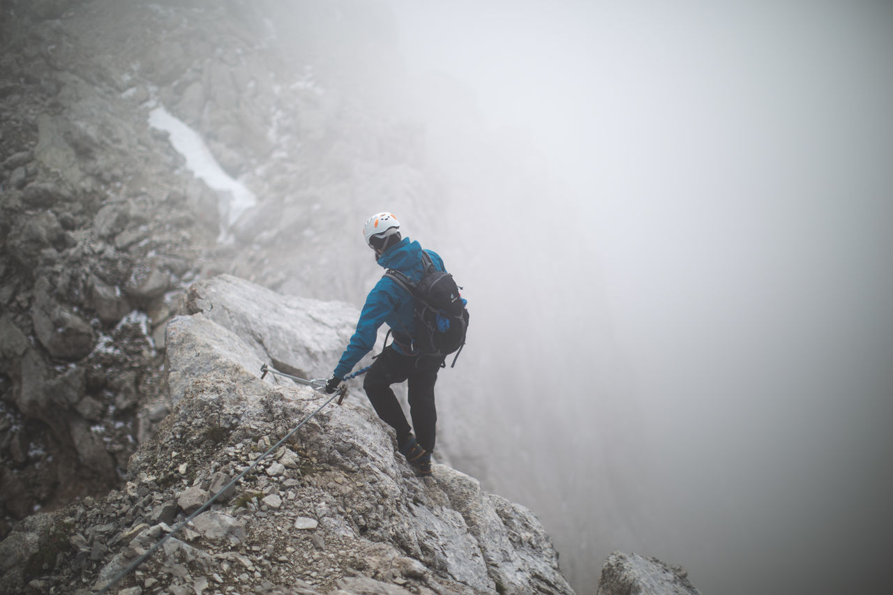 Full length rear view of hiker walking on rocky mountain during foggy weather