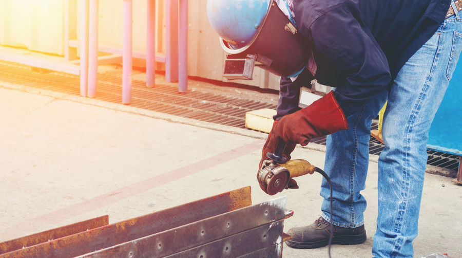 Construction worker grinding metal at site