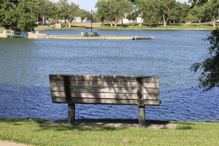 Park Bench with Blue Water and grass, Green Color Metal Post Pond Beauty In Nature Bench Boards Day Empty Grass Lake Land Nature No People Outdoors Park Park Bench Plant Scenics - Nature Seat Tranquil Scene Tranquility Tree Tree's  Water Wood - Material