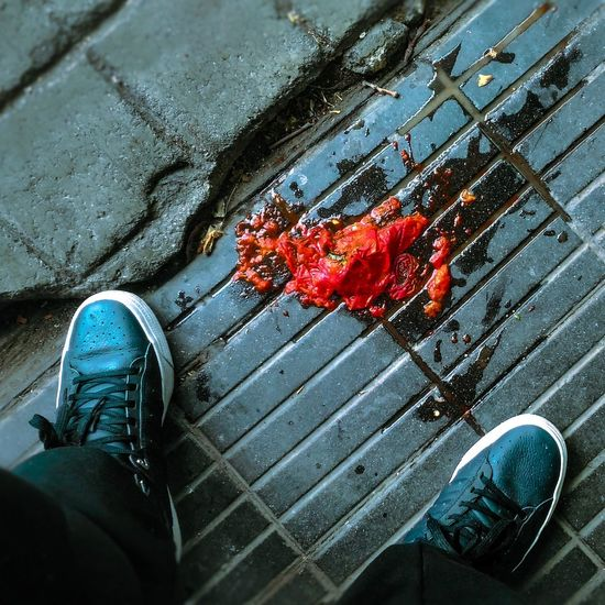Low Section Of Man Standing By Damaged Tomato On Sidewalk