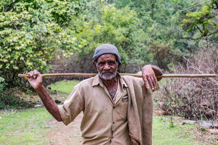Portrait of senior man holding stick on land