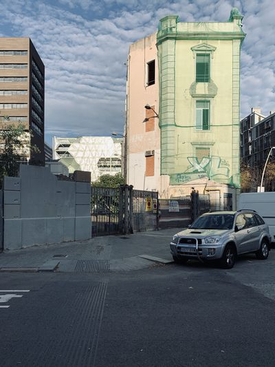 Cars on road by buildings against sky in city