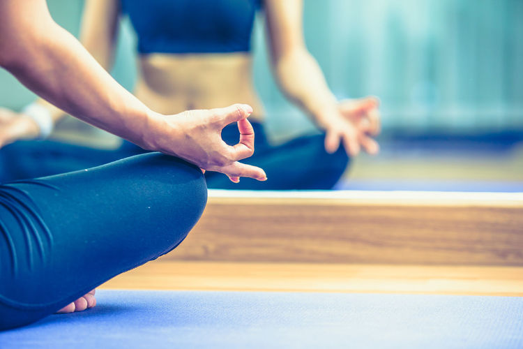 Low section of woman meditating in gym
