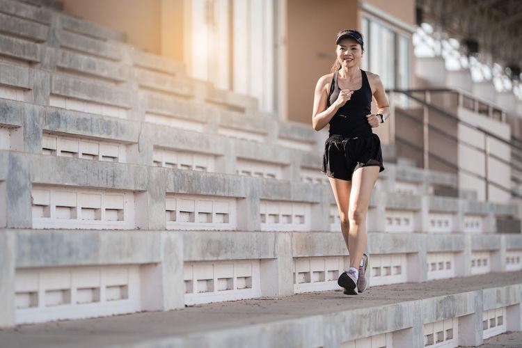 Full length of woman running in city