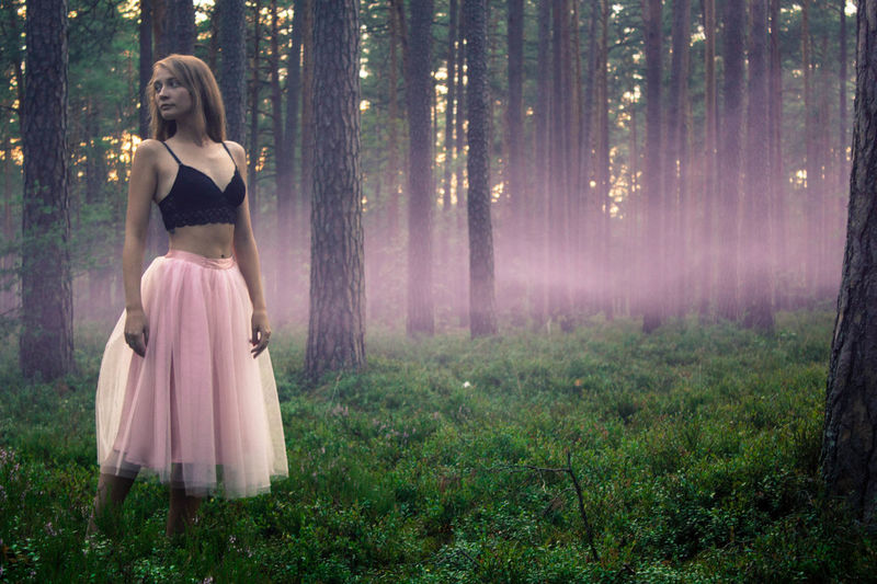 Woman looking away while standing in forest