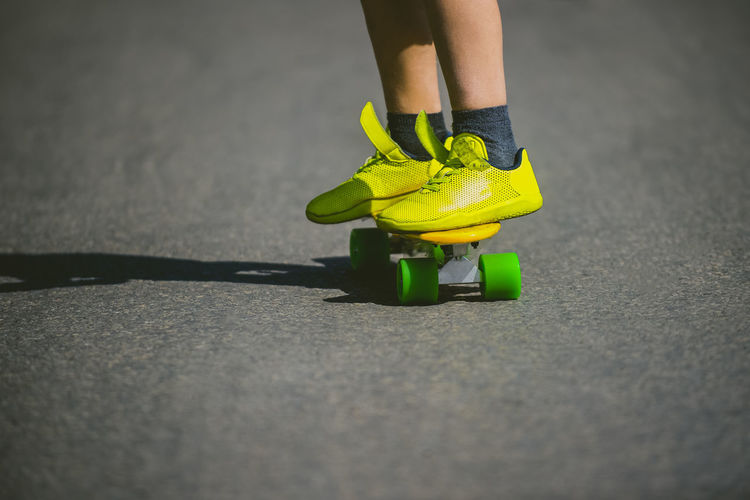 Little boy standing on a yellow skateboard pennyboard image of large children's legs on a roller foot on sports shoes on boy rides on a plastic skateboard on an asphalt Skateboarding Action Activity Body Part City Day Human Body Part Human Foot Human Leg Human Limb Leisure Activity Lifestyles Low Section One Person Real People Road Selective Focus Shoe Sport Sports Street Transportation Women Yellow Summer Sports