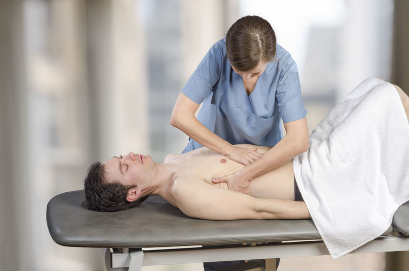 Woman Giving Massage To Man In Beauty Spa