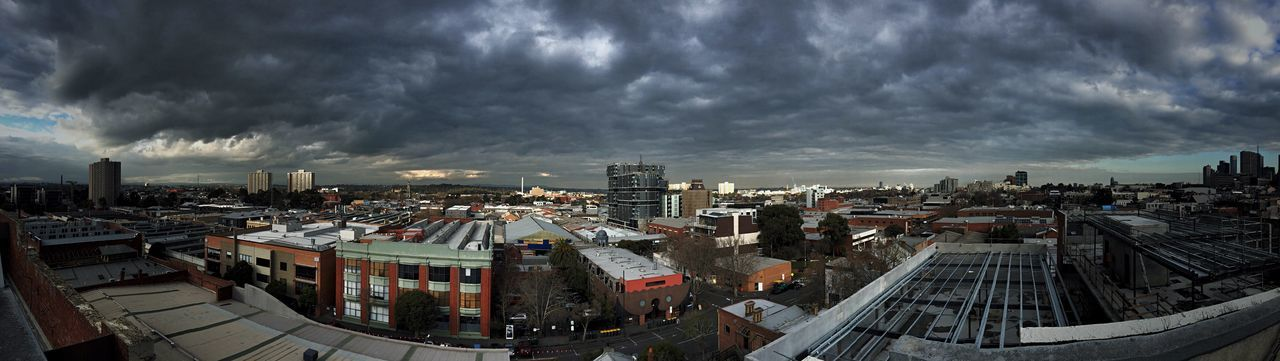 Panoramic view of residential district against cloudy sky
