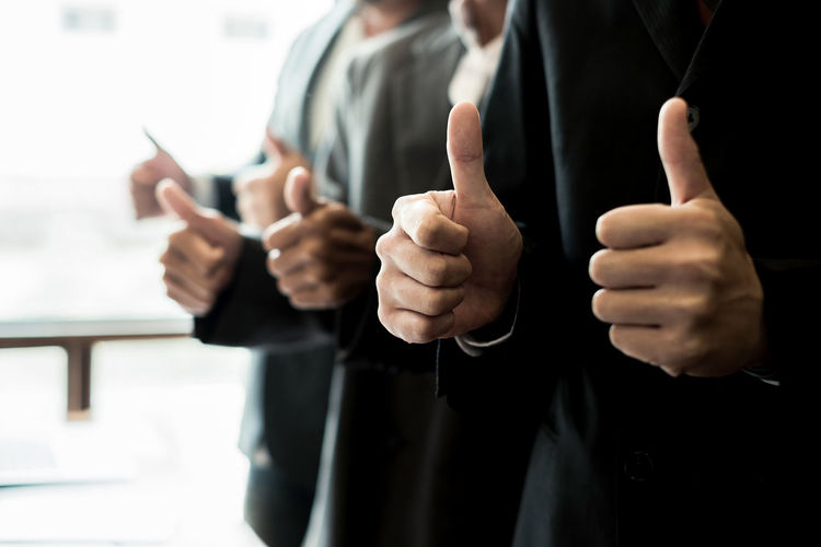 Close-Up Of Businessmen Gesturing Thumbs Up Sign At Office