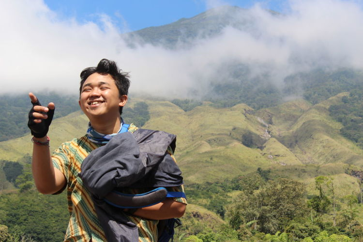 Young woman smiling against mountains