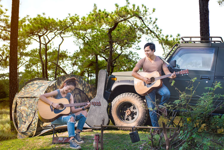 Friends playing guitars against vehicle on field