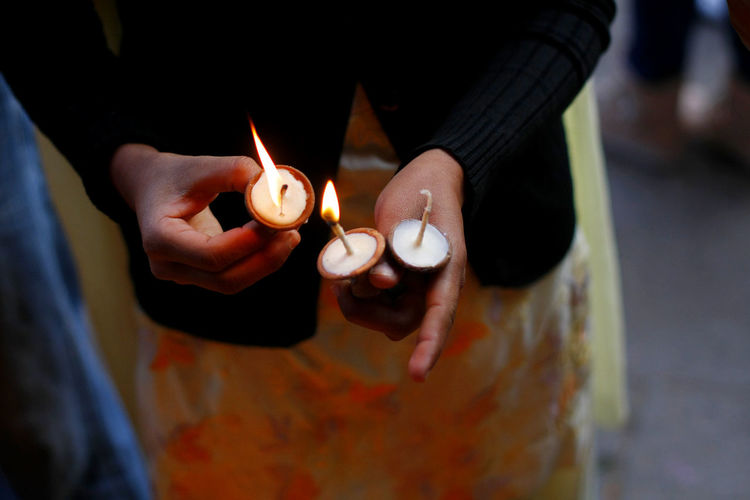 Midsection of woman igniting butter lamp at temple