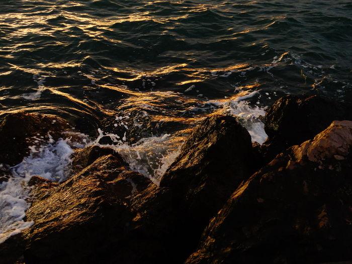 High angle view of waves splashing on rocks during sunset