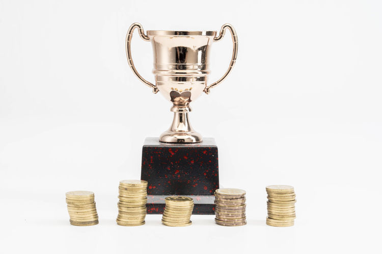 Trophy Cup and coins Studio Shot Finance White Background Coin Indoors  Stack Still Life Business Wealth Currency Gold Colored Success Large Group Of Objects No People Savings Metal Investment Achievement Container Economy