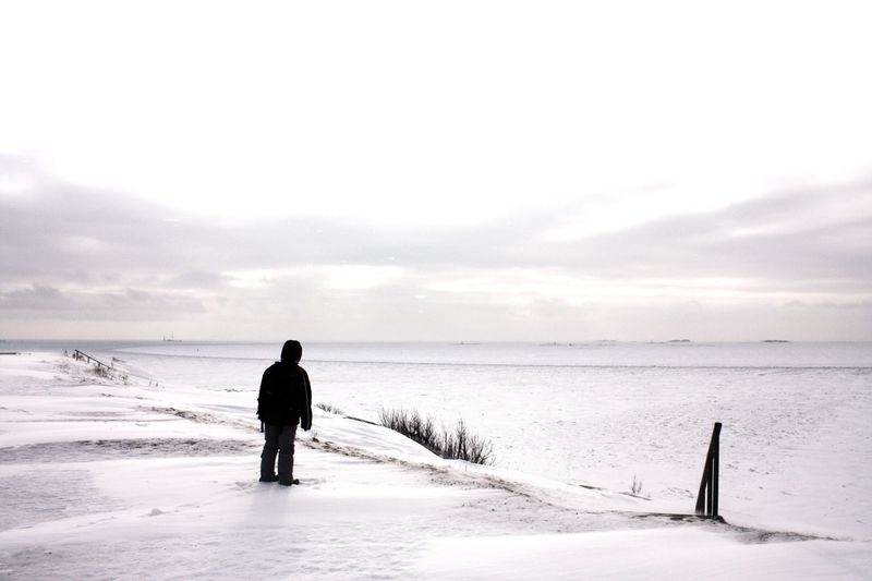 Rear View Of Man Standing At Beach Against Sky During Winter