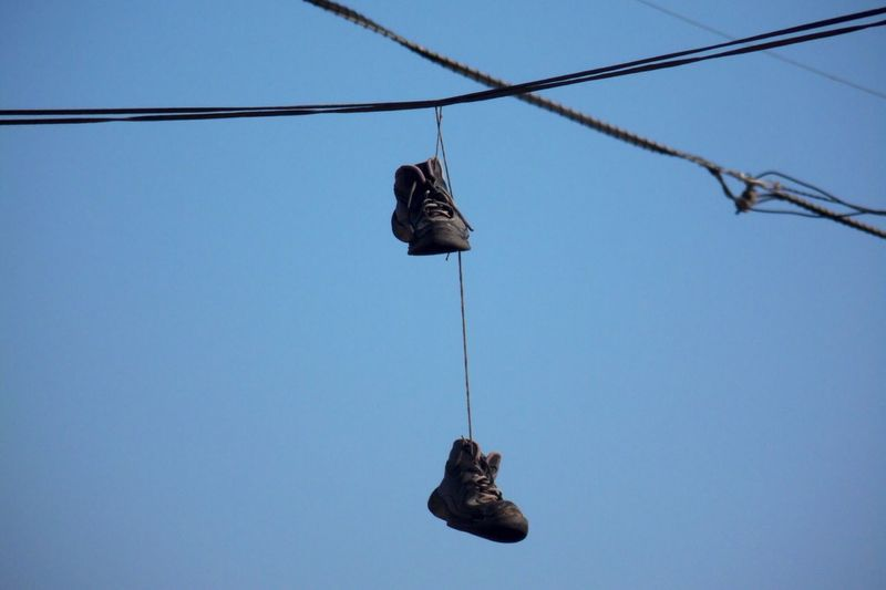 Shoes hanging on cable against clear sky