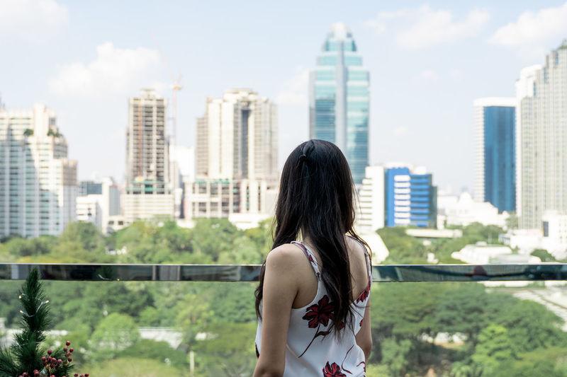 Woman standing against modern buildings in city