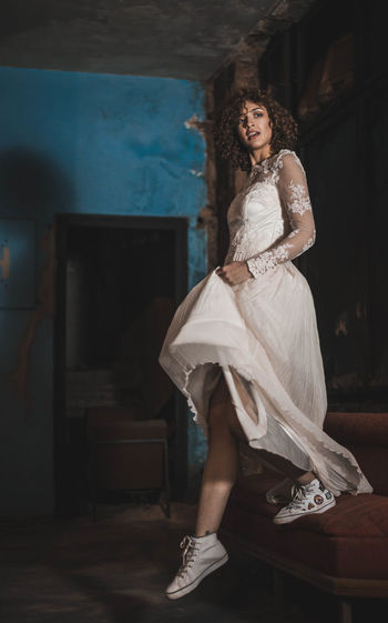 Full Length Of Sensuous Young Woman In Wedding Dress Jumping From Sofa At Home