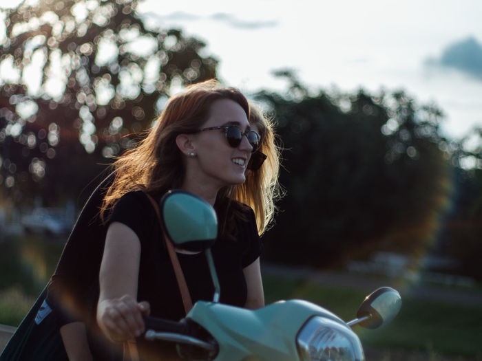 Young woman wearing sunglasses sitting on motor scooter against trees