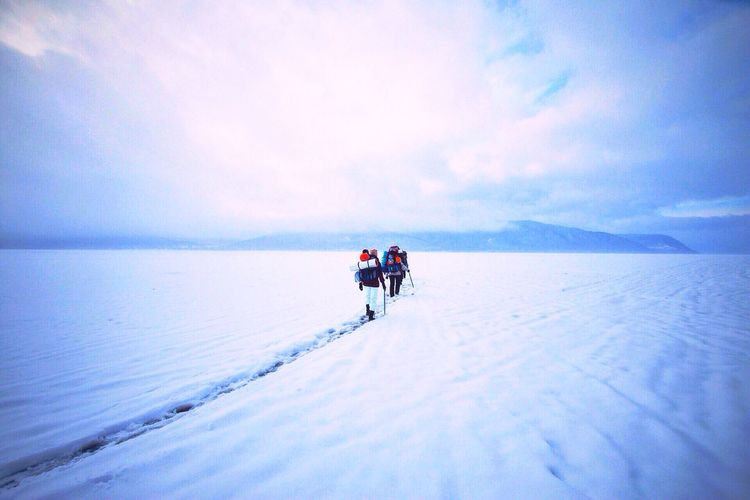 Rear view of hikers walking on snow covered field against cloudy sky