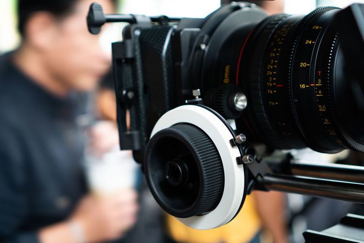 Close-up of camera with man in background
