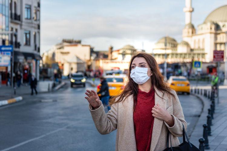 Woman wearing mask looking away standing on street