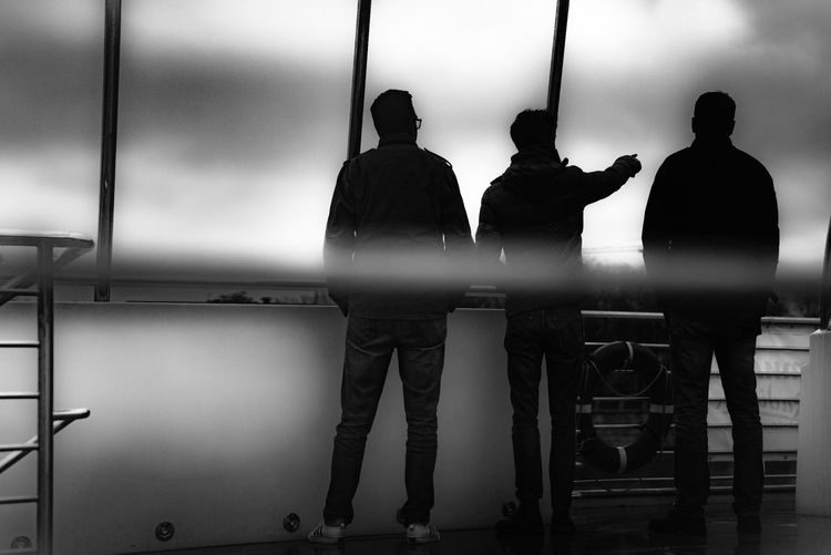 Rear view of silhouette people standing against railing
