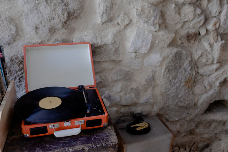 High Angle View Of Turntable In Suitcase Against Wall