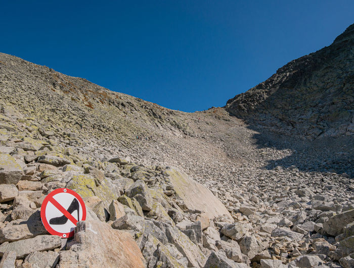 Road sign on rocks against clear blue sky