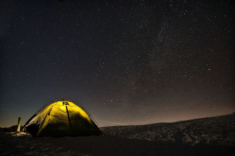 Scenic view of mountain and tent against sky at night