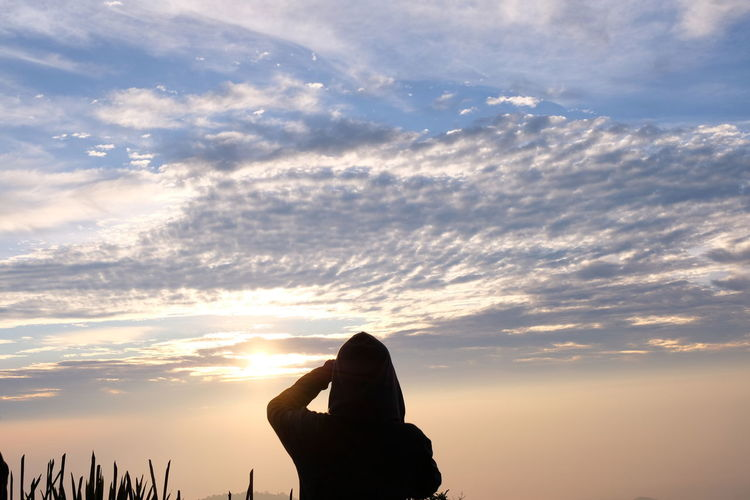 Silhouette person shielding eyes while standing against sky during sunset