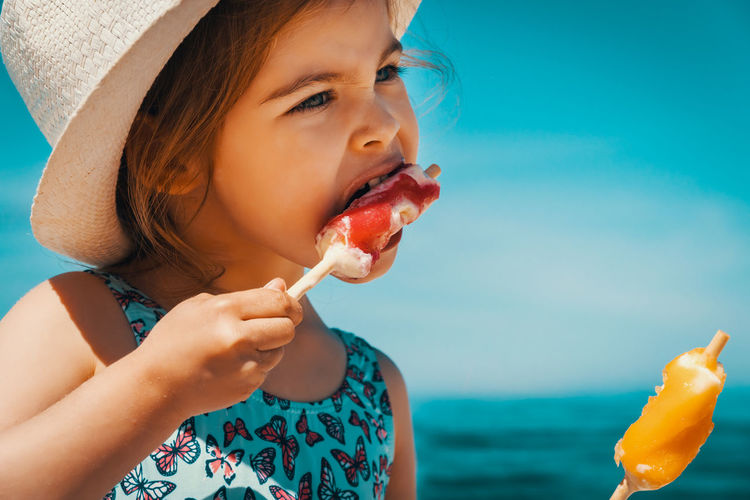 Summer Child Girl Kid Sea Beach Water Sky Ice Cream Childhood Food And Drink Food One Person Eating Leisure Activity Lifestyles Real People Girls Headshot Close-up Hat Clothing Innocence Outdoors Horizon Over Water Sun Hat
