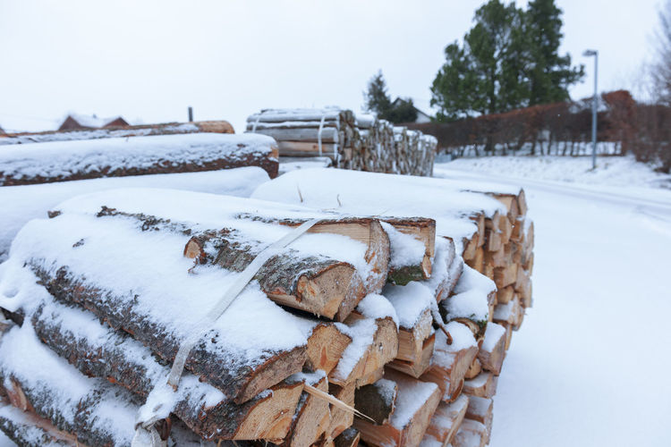 Stack of logs on snow covered field