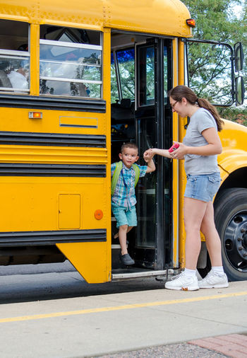 A young mother collects her son off the school bus at the end of the day Colorado Family Home Young Child Childhood Collecting Child Day Full Length Hispanic Kid Motion Outdoors People Real People School Bus School Safety Togetherness Transportation Two People Yellow Young Adult