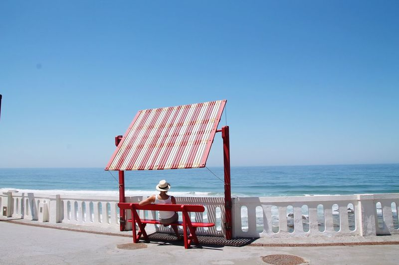 Rear View Of Woman Sitting On Bench At Promenade Against Clear Blue Sky