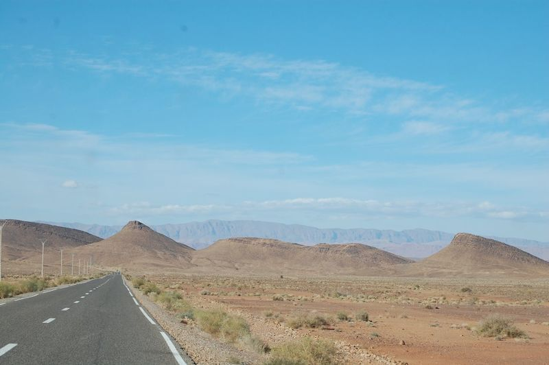 Empty road with mountain range in background