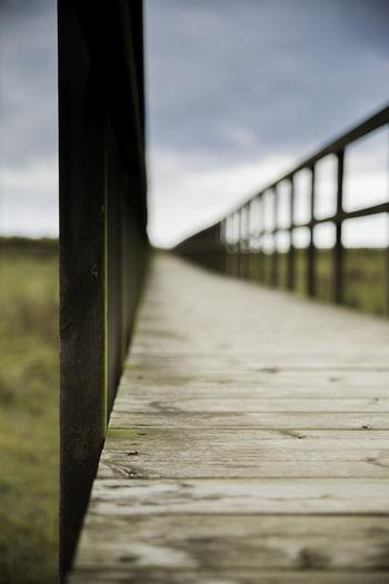 Surface level of wooden bridge against sky