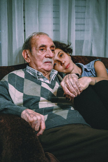 Portrait of woman with father sitting on sofa at home