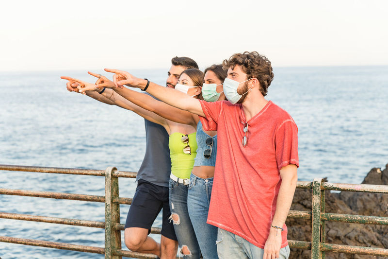 Friends wearing mask pointing away standing by railing against sky