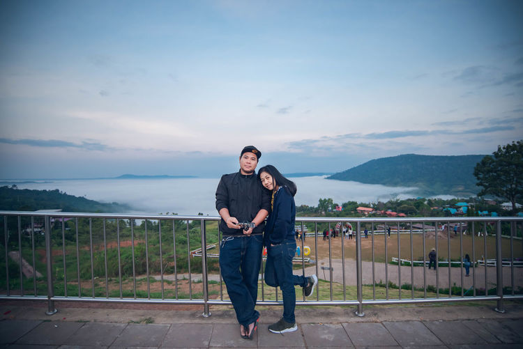 Full length portrait of couple standing against railing and sky