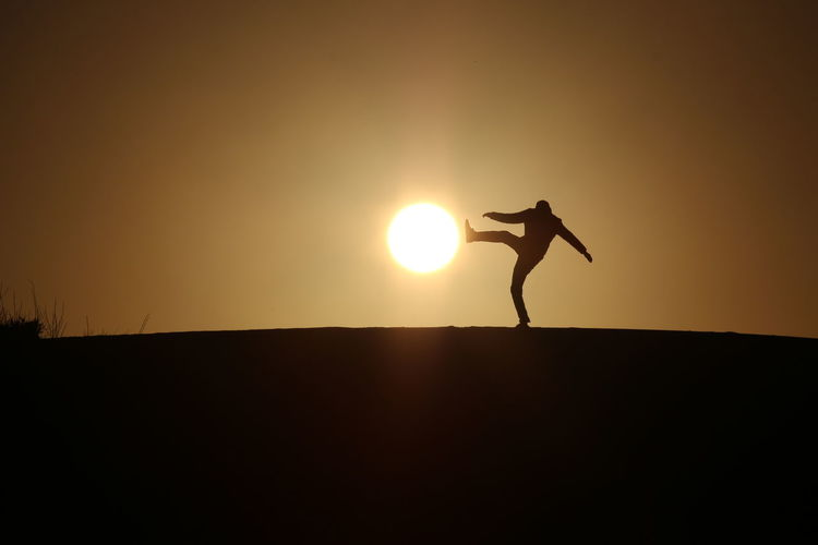 Silhouette man kicking son while standing on landscape against sky during sunset