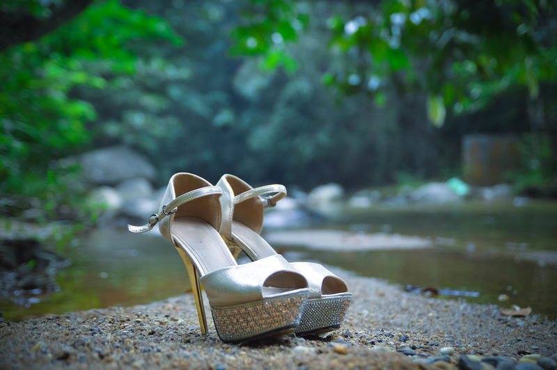 Close-up of high heels by stream at forest