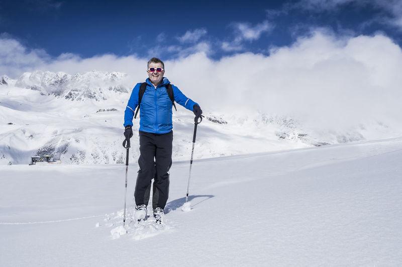 Full Length Of Smiling Man Standing On Snow Covered Landscape
