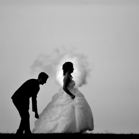 Side view of bride and groom against sky