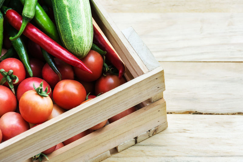 High angle view of tomatoes in wooden container on table