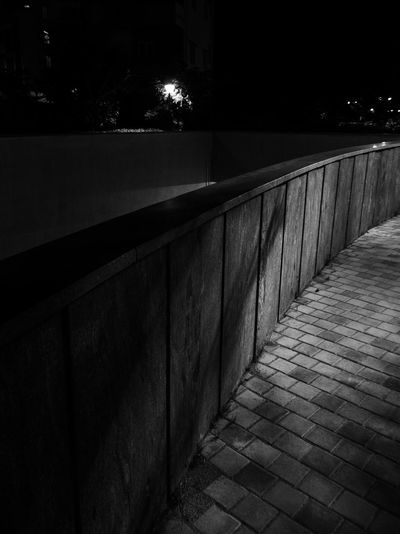 View of empty footpath at night
