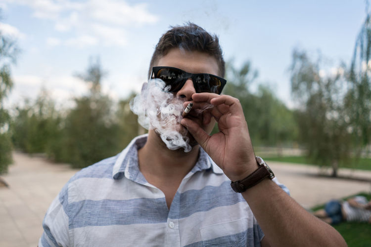 Smoking Cigarette  Day Facial Hair Fashion Focus On Foreground Front View Glasses Headshot Holding Human Body Part Human Face Leisure Activity Lifestyles Looking At Camera Men Obscured Face One Person Portrait RISK Smokin Sunglasses Young Adult Young Men