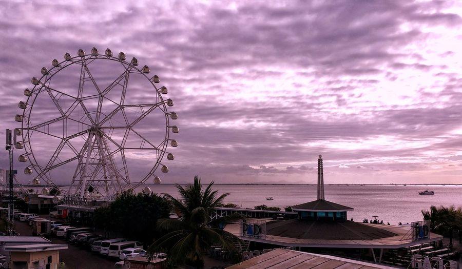 Amusement park against sky at sunset