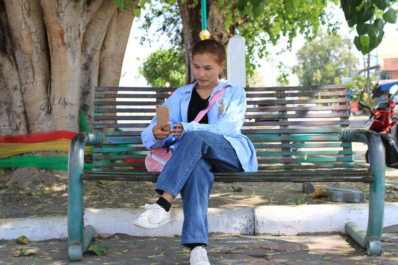 Full length of young woman using smart phone while sitting on bench